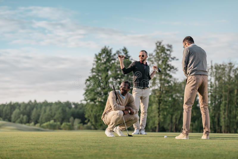 Multicultural friends spending time together while playing golf on golf course royalty free stock image