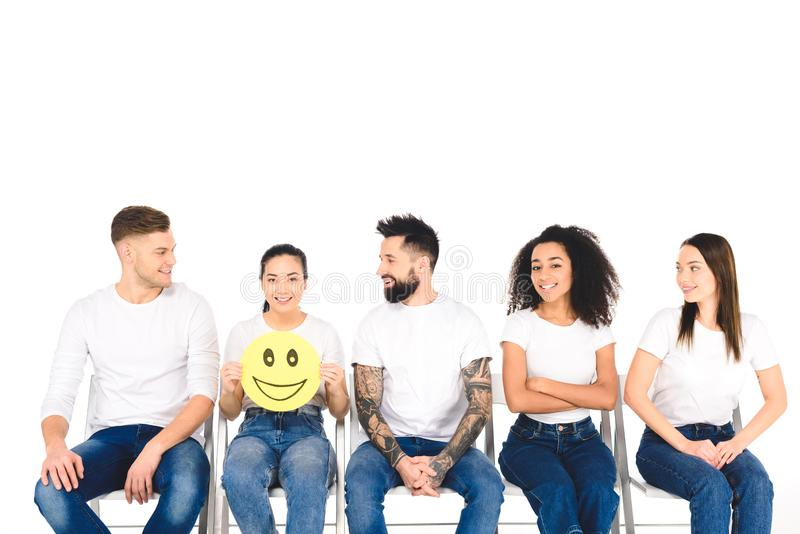 multicultural friends in white t-shirts looking at girl with happy sign isolated royalty free stock images