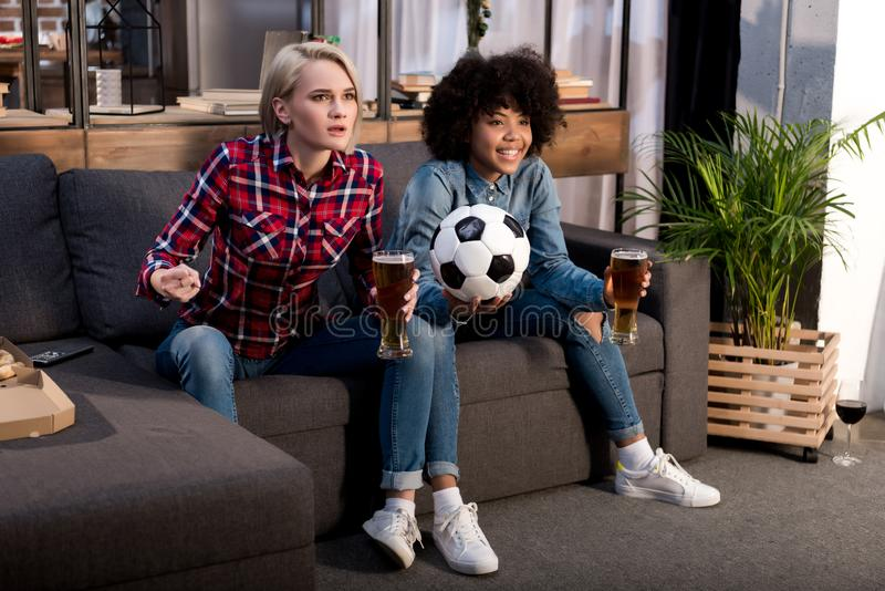 multicultural girls watching football on tv royalty free stock photo