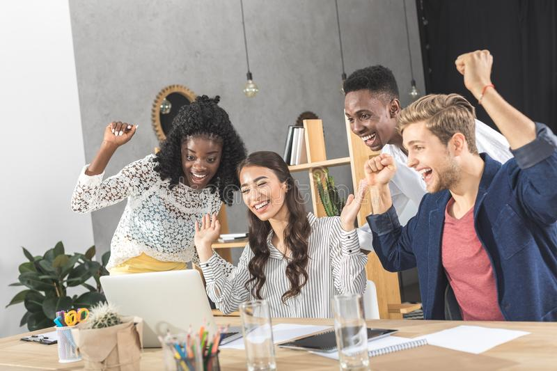 Multicultural group of business people celebrating success at workplace. With laptop stock photography