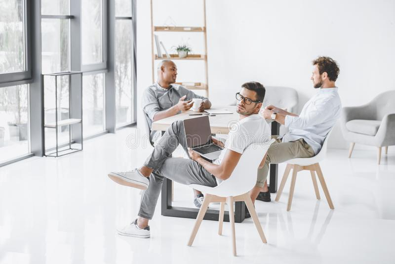 multicultural group of businessmen sitting at workplace in light stock photo