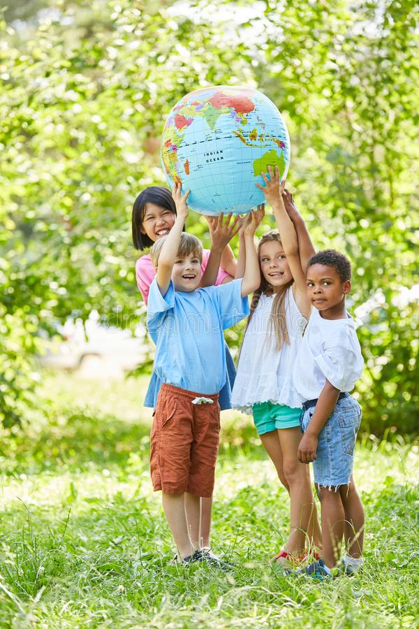 Multicultural group of kids holds world globe royalty free stock image