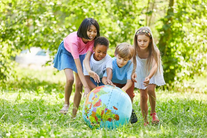 Multicultural group of kids rolls world globe royalty free stock image
