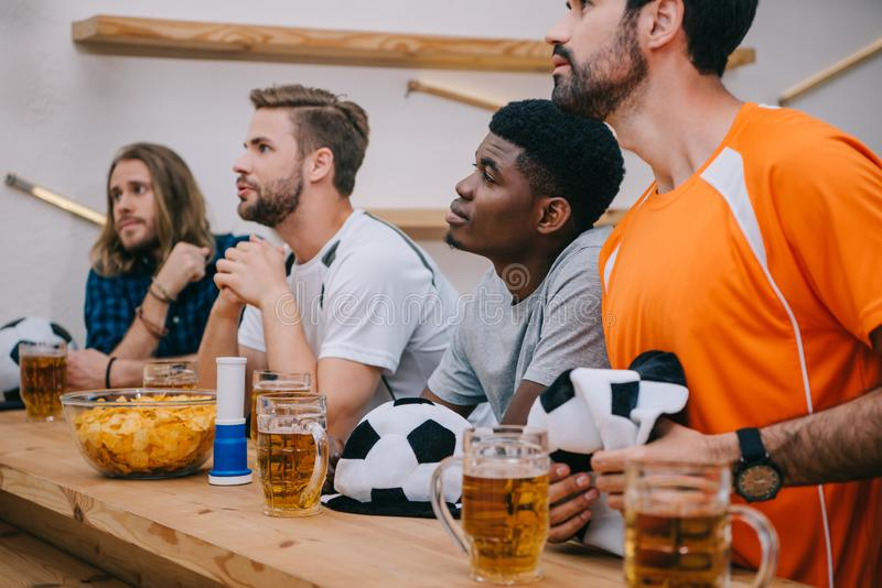 multicultural group of male football fans with soccer ball hats fan horn chips and beer watching soccer match stock photo