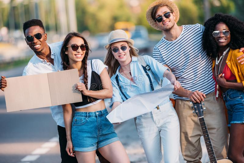 multicultural group of young hitchhikers with map and empty cardboard standing at sidewalk stock photos