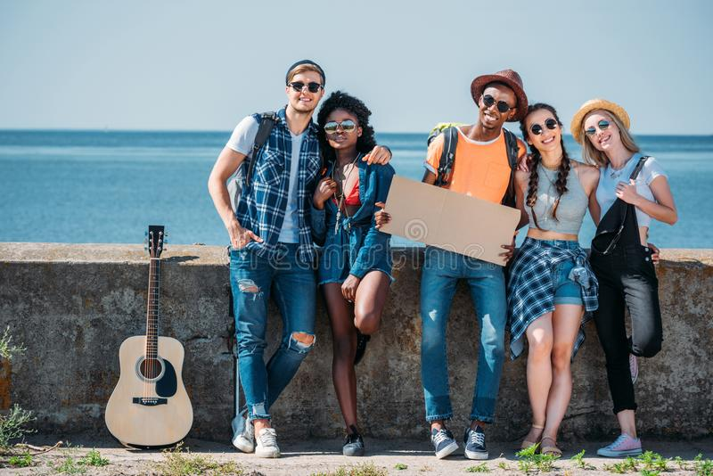 multicultural group of young people with empty cardboard standing a parapet while royalty free stock photography