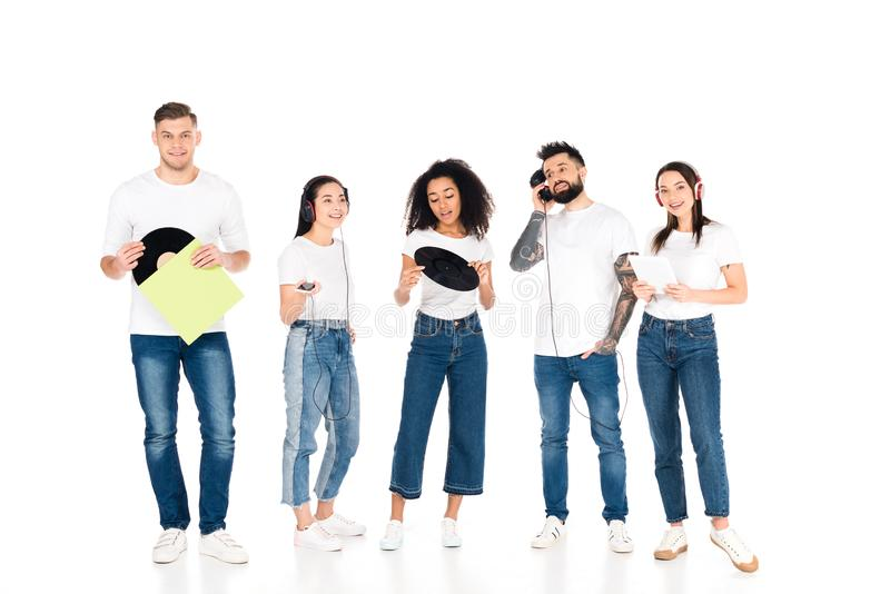 Multicultural group of young people listening music in headphones and holding vinyl records isolated. On white stock photography