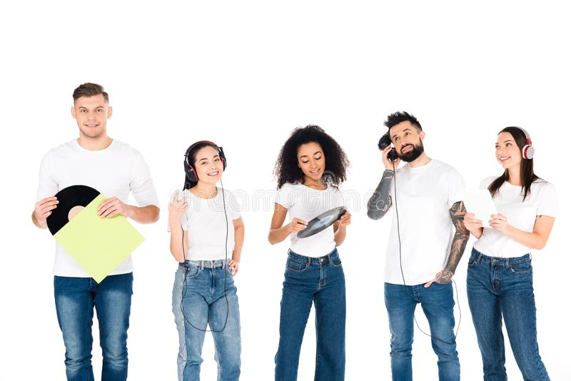Multicultural group of young people listening music in headphones and holding vinyl records isolated. On white stock photos