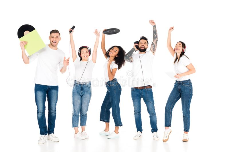 Multicultural group of young people with raised hands listening music in headphones and holding vinyl records isolated. On white royalty free stock photography