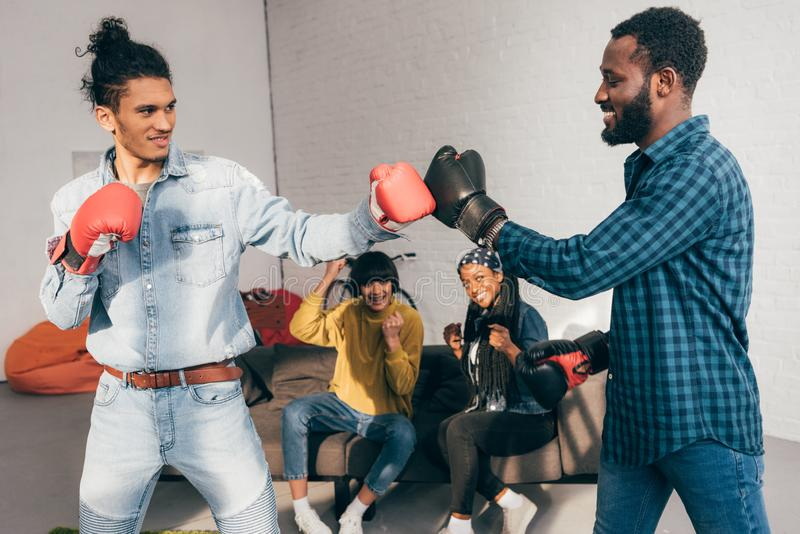 multicultural male friends doing sparring in boxing gloves and two women cheering royalty free stock image