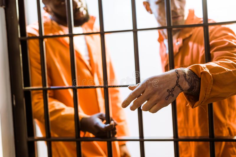 multicultural prisoners standing near prison bars stock photo