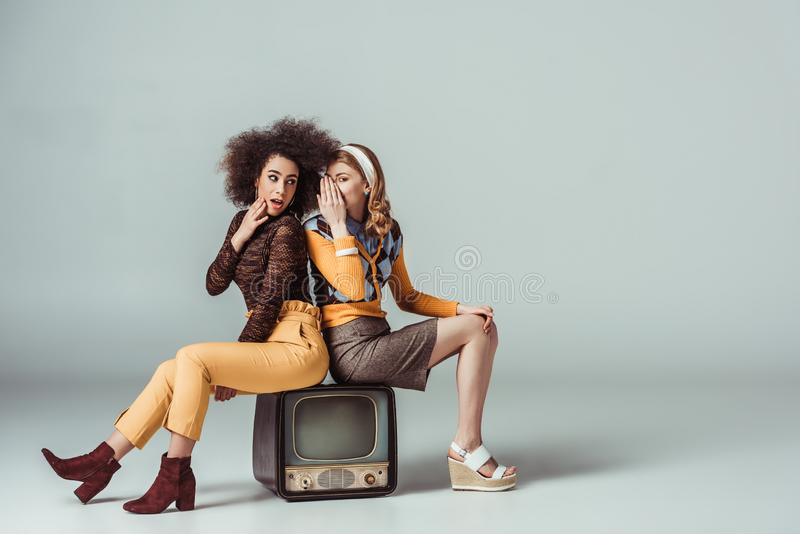 Multicultural retro styled girls gossiping and sitting. On vintage television stock images