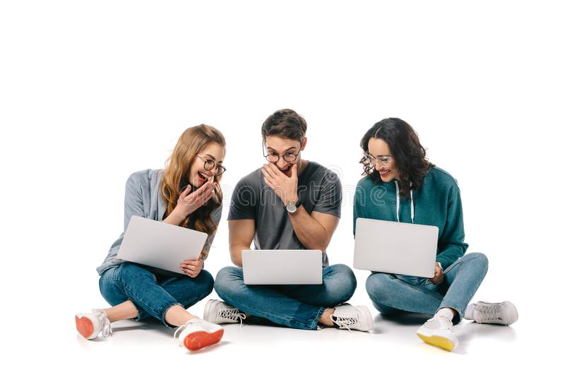 Multicultural students laughing and using laptops. On white stock image