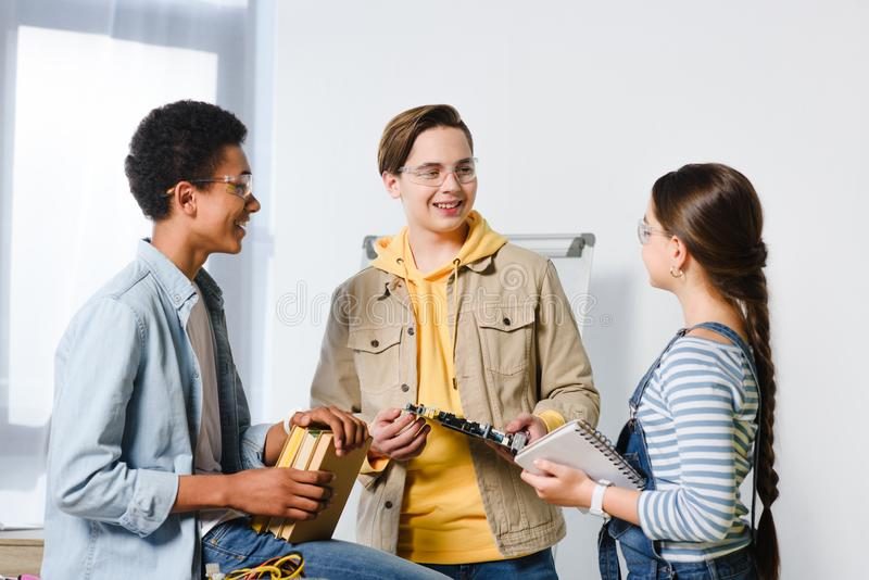 Multicultural teenagers with computer circuit and books. At home royalty free stock photography