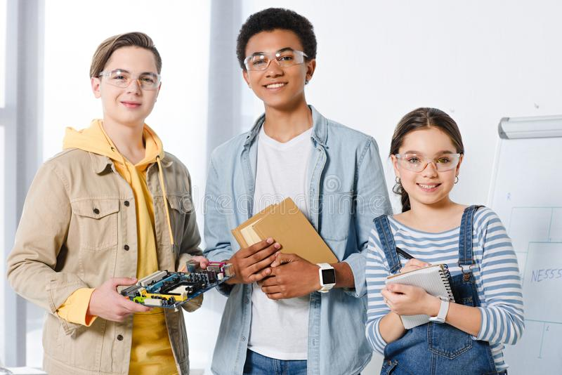 Multicultural teenagers holding computer motherboard and books. At home stock image