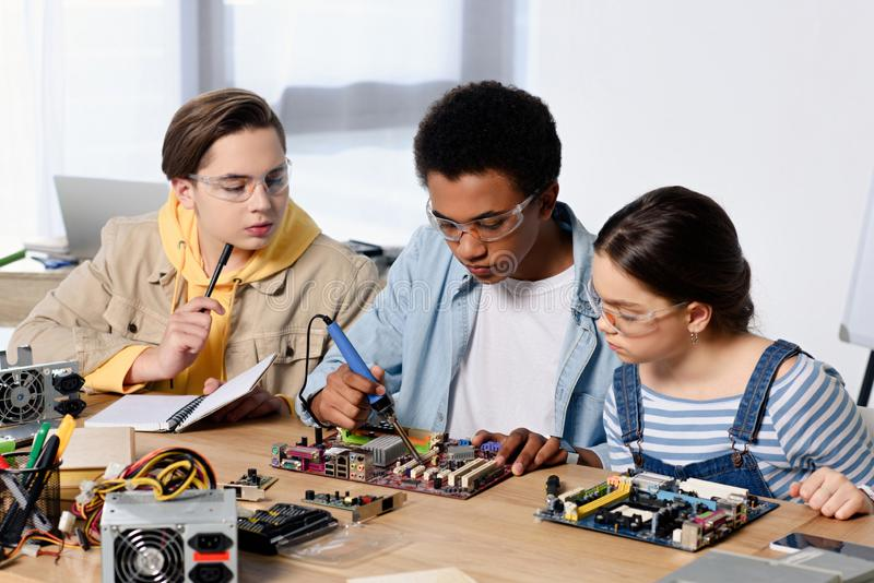 Multicultural teenagers soldering computer circuit with soldering iron. At home stock photo