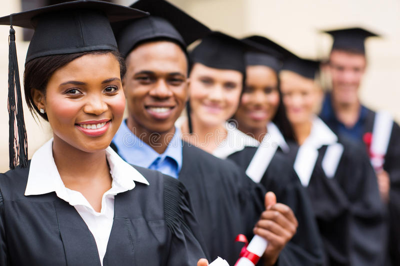 Multicultural university graduates. Group of multicultural university graduates standing in a row royalty free stock image