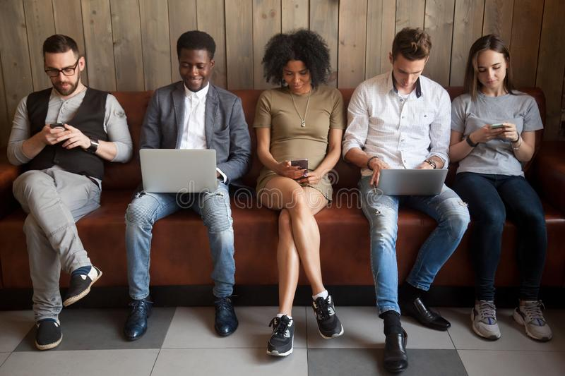 Multicultural young people using laptops and smartphones sitting. In row, diverse african and caucasian millennials entertaining online obsessed with modern stock image