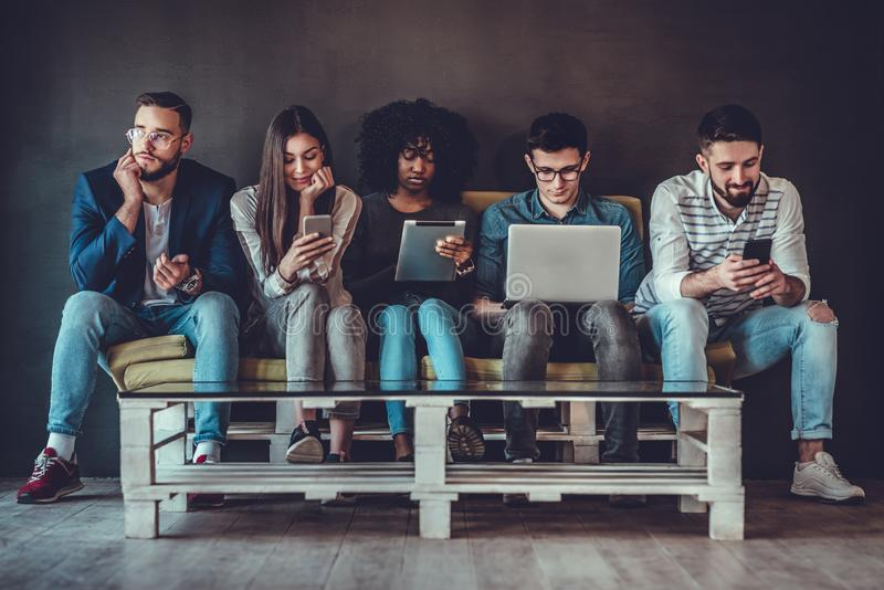 Multicultural young people using laptops and smartphones sitting in row stock photos
