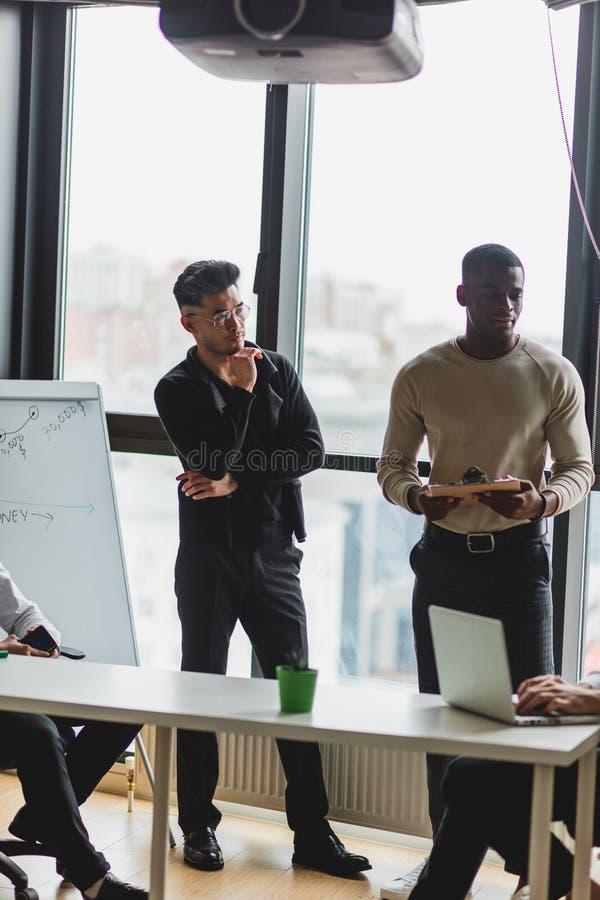 Multiculturele bedrijfsmensen die in conferentieruimte werken stock afbeelding
