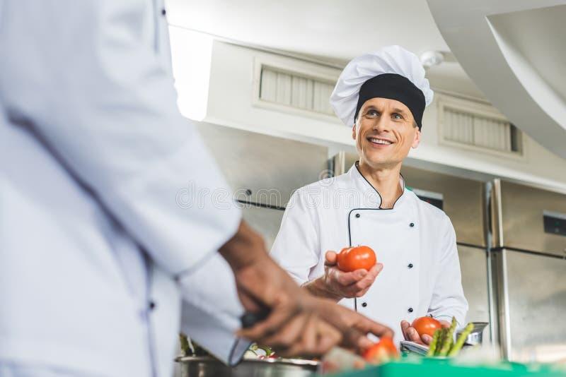 multiculturele chef-koks die salade voorbereiden royalty-vrije stock afbeeldingen