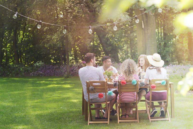Multiculturele groep vrienden die lunch in de tuin op s eten royalty-vrije stock foto's