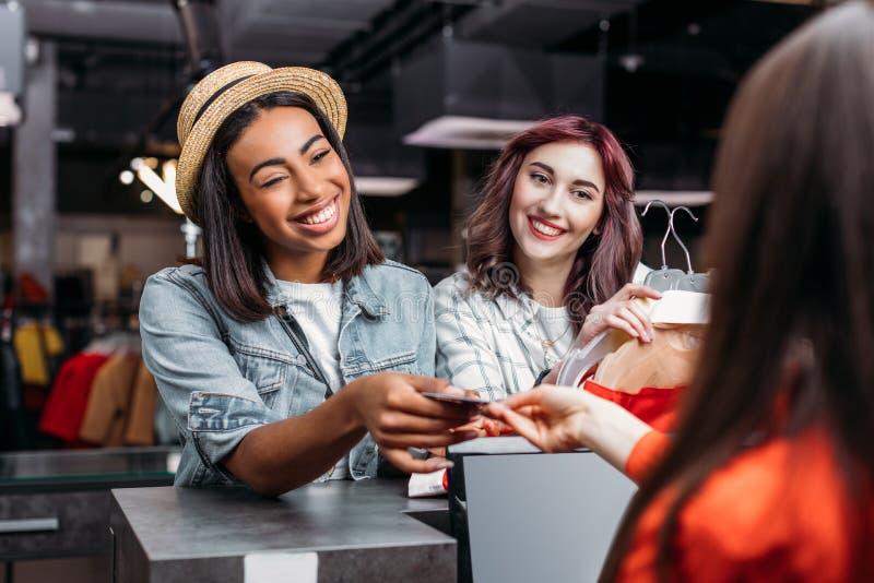 Multiculturele jonge meisjes die en met creditcard in boutique winkelen betalen stock foto's