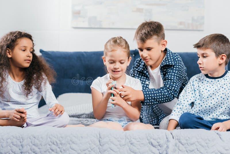 multiculturele kinderen die met smartphone samen op bed rusten stock afbeelding