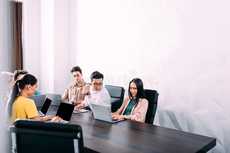 multiculturele partners die vergadering hebben bij lijst met laptops in modern stock afbeelding