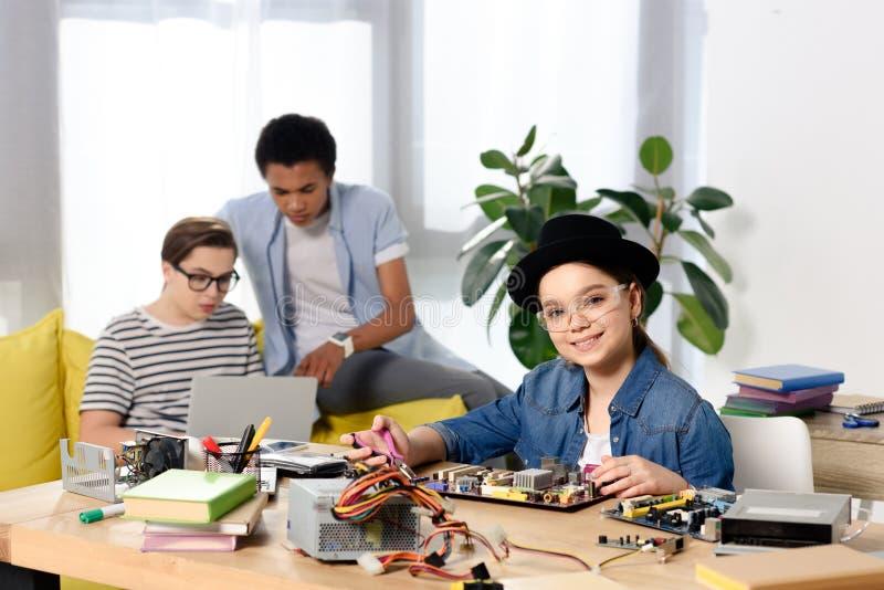 multiculturele tienerjongens die laptop en vrouwelijke jong geitje het bevestigen computermotherboard met behulp van royalty-vrije stock foto