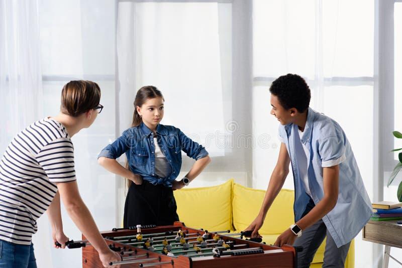 multiculturele tienerjongens lijstvoetbal spelen en vrouwelijke vriend die zich met met de handen in de zij handen bevinden stock foto's