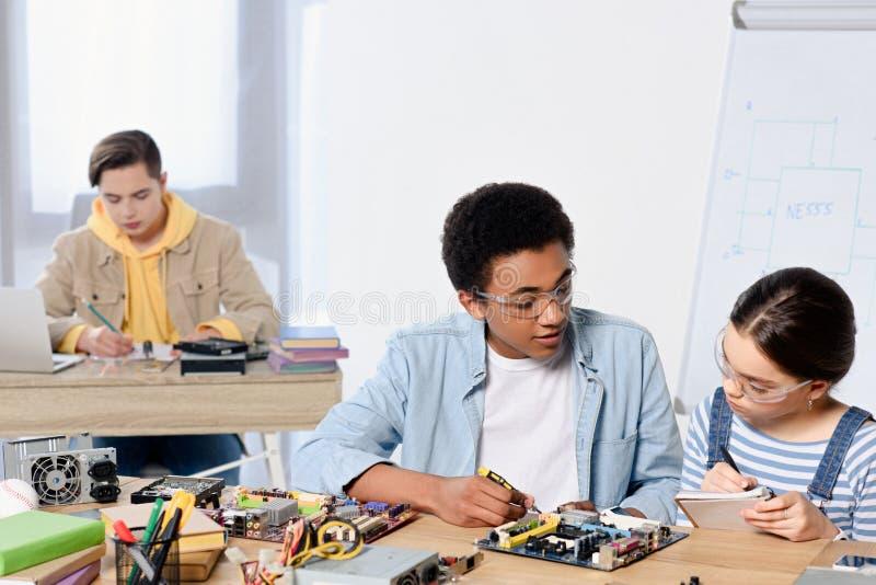 multiculturele tieners die computermotherboard bevestigen stock afbeeldingen