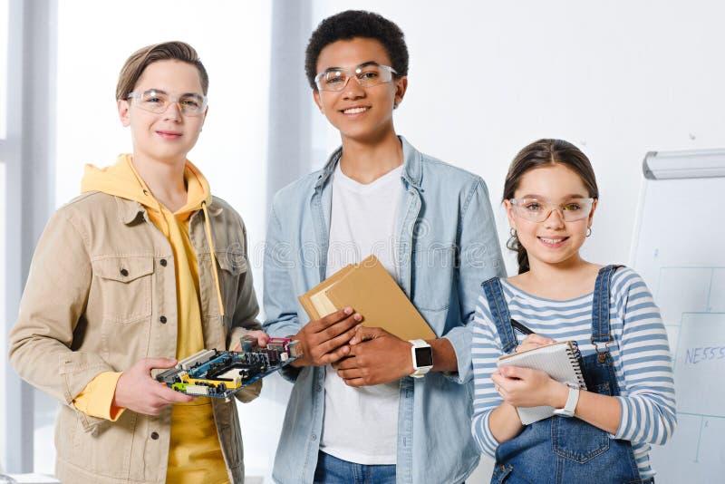 multiculturele tieners die computermotherboard en boeken houden stock afbeelding