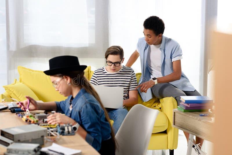 multiculturele tieners die met laptop en computermotherboard bestuderen royalty-vrije stock afbeelding