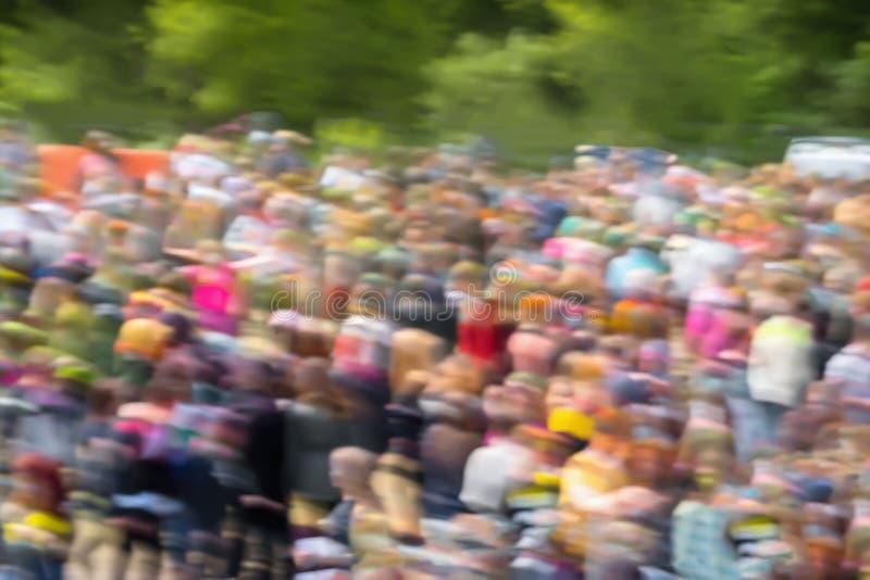 Multidão abstrata de jovens irreconhecíveis muito borrados, fundo colorido brilhante, foco seletivo imagem de stock