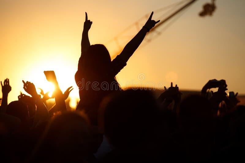 A multidão aprecia o festival de música do verão, por do sol, as mãos das silhuetas acima imagens de stock