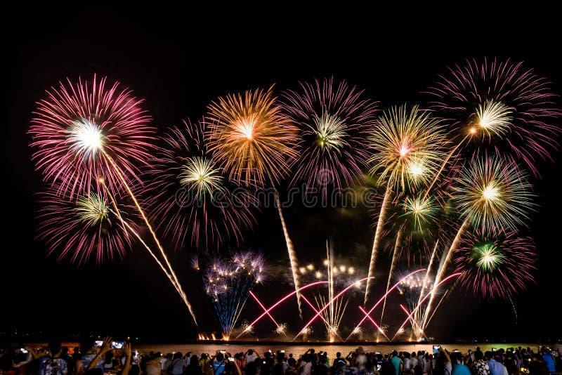 Multidão Cheering que olha fogos de artifício coloridos e que comemora na praia durante o festival fotografia de stock