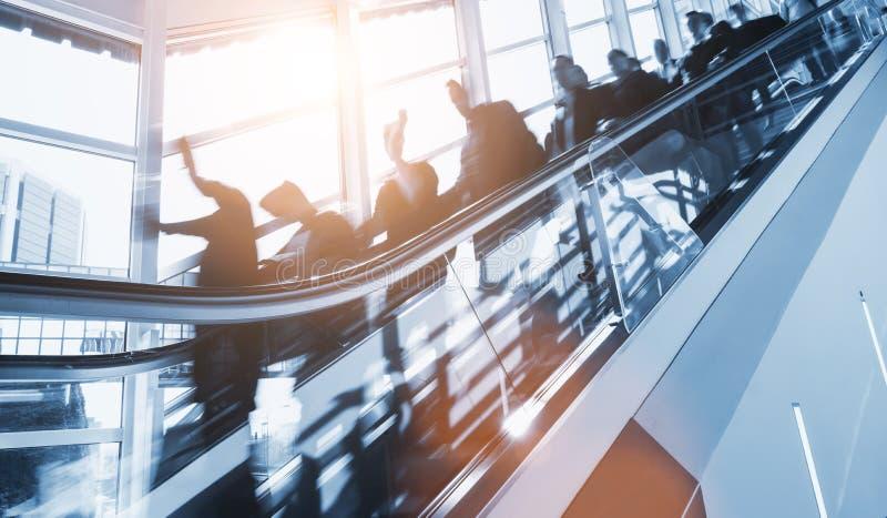 Multidão de executivos borrados anônimos que apressam-se em um escalato fotos de stock royalty free