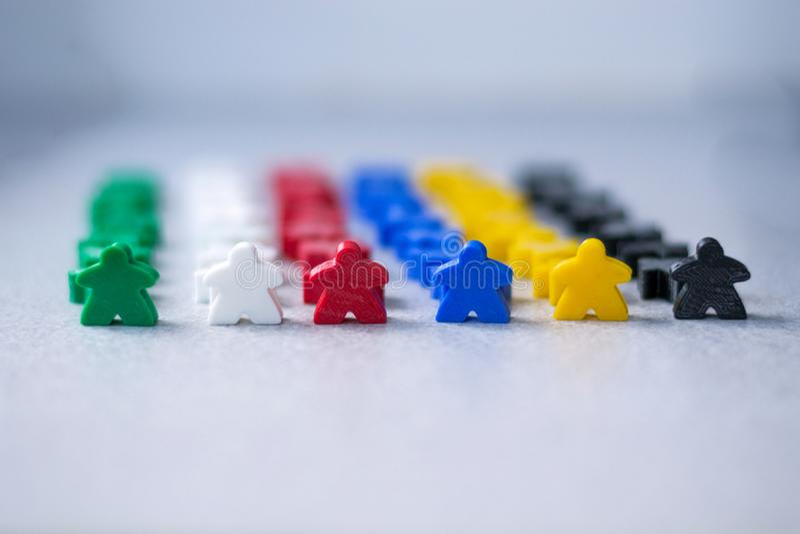 Multidão de figuras pequenas coloridas dos povos como um conceito de teambulding Meeples do jogo de mesa Estratégia empresarial e imagem de stock