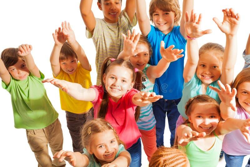 Multidão de mãos da elevação das crianças até a câmera fotografia de stock royalty free