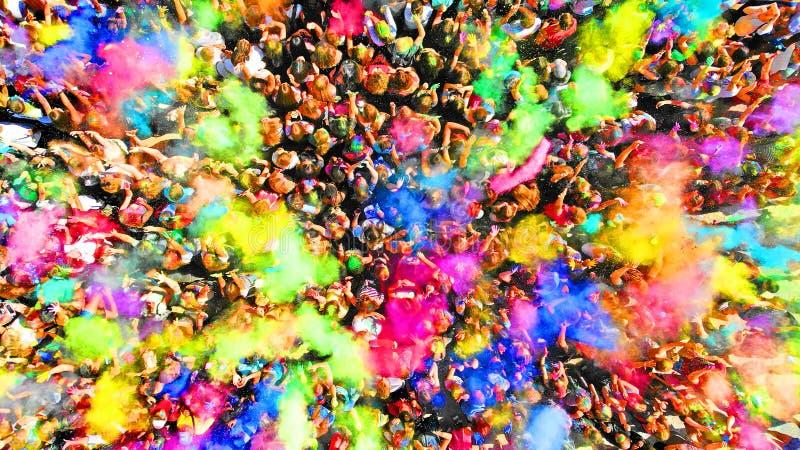 Multidão de povos em um festival das cores de Holi aéreo Respingo da pintura em uma multidão de opinião dos povos acima imagens de stock royalty free