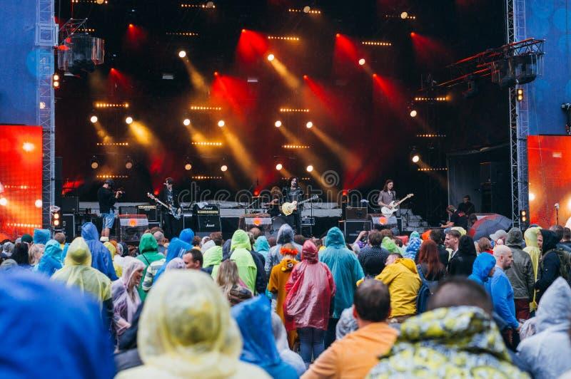 Multidão nas capas de chuva durante o preformance do festival