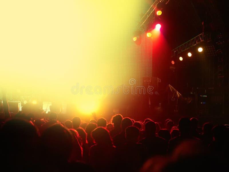 Multidão no concerto de rocha na frente da fase iluminada imagens de stock