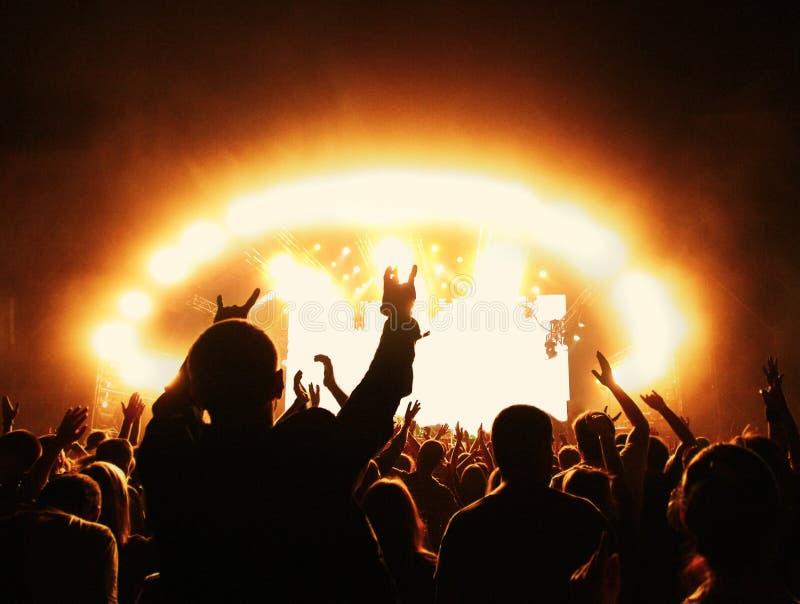 Multidão no concerto de rocha na frente da fase iluminada fotos de stock