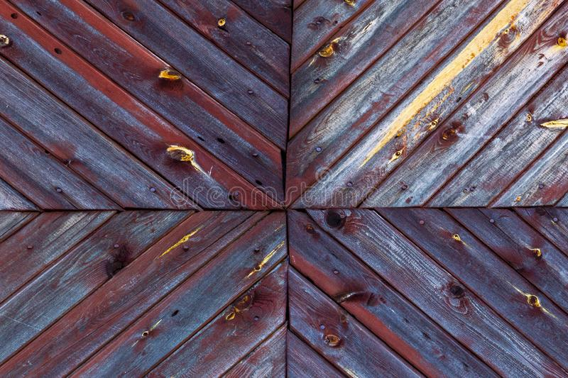 Multidirectional painted wooden plank on the facade of an old country house in Siberia. royalty free stock images