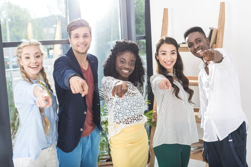 multiethnic χαμογελώντας επιχειρηματίες που δείχνουν στη κάμερα στεμένος από κοινού στοκ εικόνες με δικαίωμα ελεύθερης χρήσης