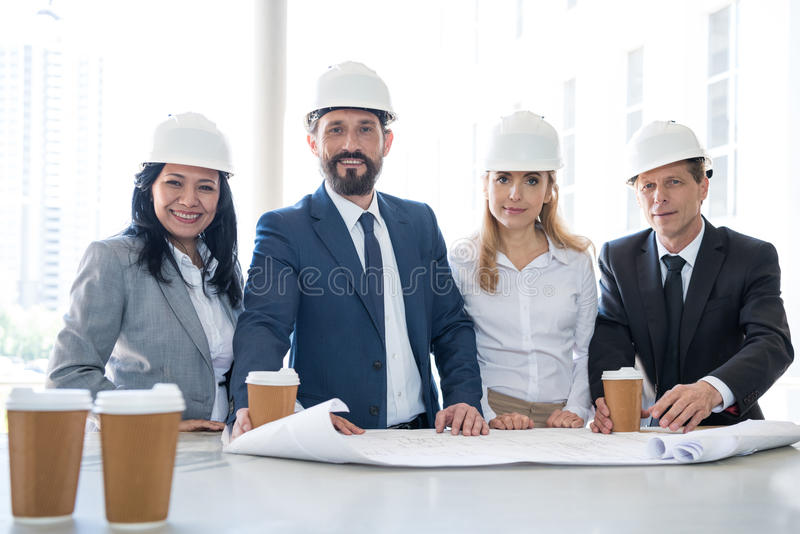 Multiethnic architects in formal wear looking at camera. Smiling multiethnic architects in formal wear looking at camera stock image