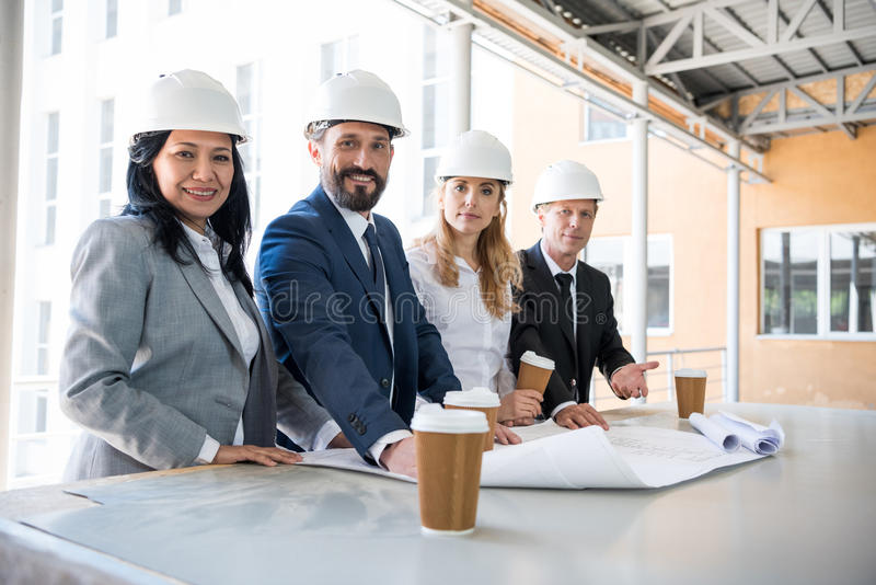 Multiethnic architects in suits looking at camera while working with blueprints. Group of multiethnic architects in suits looking at camera while working with stock photos