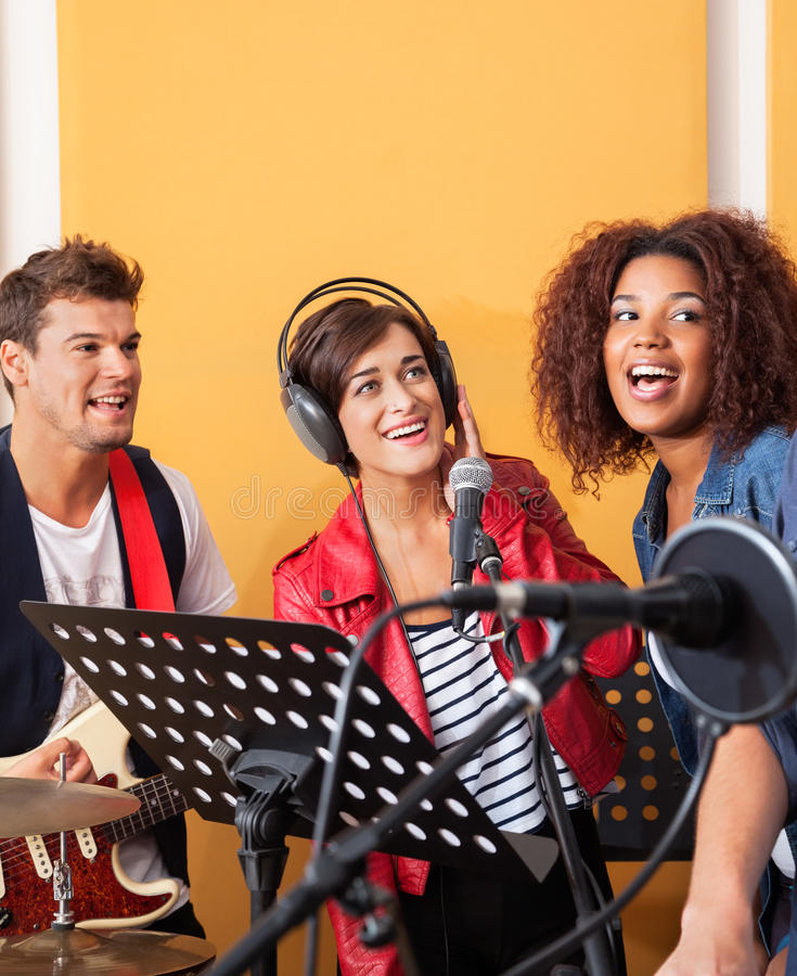 Multiethnic Band Members Performing While Looking. Happy multiethnic band members performing while looking away in recording studio stock image