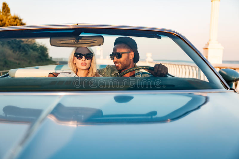 Multiethnic beautiful young couple driving car royalty free stock photos